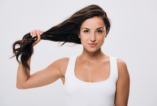 A beautiful girl in white undershirt is holding her brown strong and healthy hair in her hand
