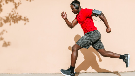 A black guy in red t-shirt and headphones is running on the street