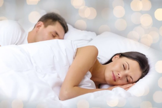 A couple sleeps on the side on the white bed