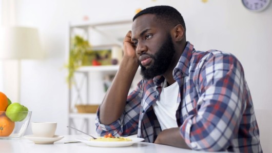 a man sitting at the table with the plate on and not eating. The man lost his appetite