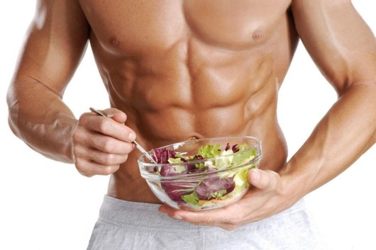 A strong and muscly guy holding a plate with vegetables
