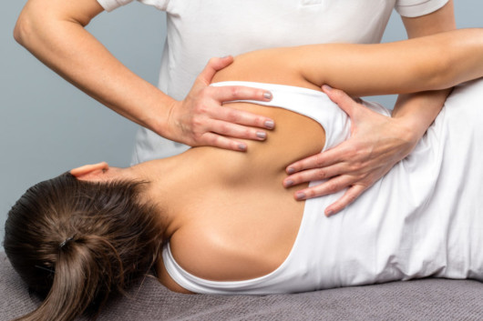 A chiropractor is helping the girl to realign your body and ease the pain
