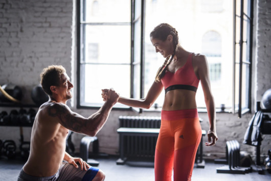 A girl and a woman are exercising in the gym and helping each other