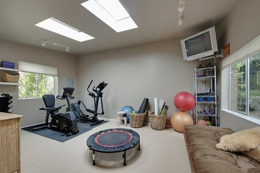 A room with fitness equipment and fitness gear, tv and sofa