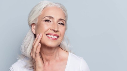 A beautiful middle aged woman is smiling and touching her firm and young skin
