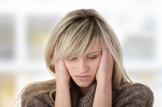 A blonde woman is depressed and holding her head with her hands
