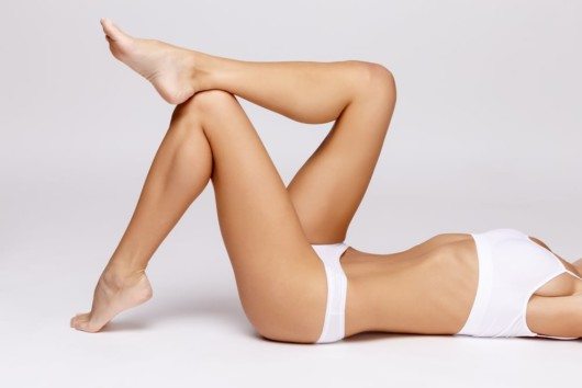 Slim girl in white underwear is lying on white background and show her slim legs after coolsculping