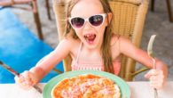A little girl is sitting at the table with knife and fork in front of the pizza and smiling