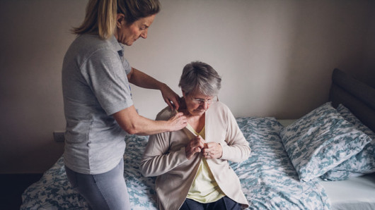 A young girl is helping to an old lady to undress. The old lady sits on the bed and trying to undress