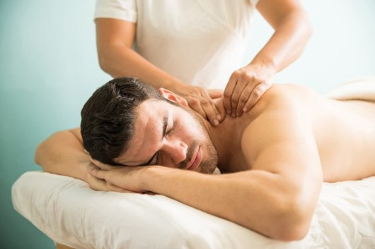 A handsome man is lying on the white bed at the massage
