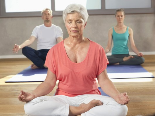 One man and two women are meditating in the room