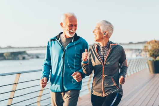 An old couple is exercising outside. An old woman and a man are running on the street and laughing. the are having fun when exercising