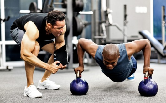 personal trainer is cheering up the man who is doing push ups on the kettlebells