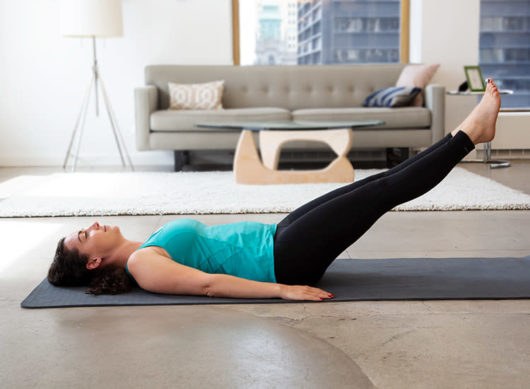 A woman in a green fitness top and black leggings is doing postpartum belly exercises at home