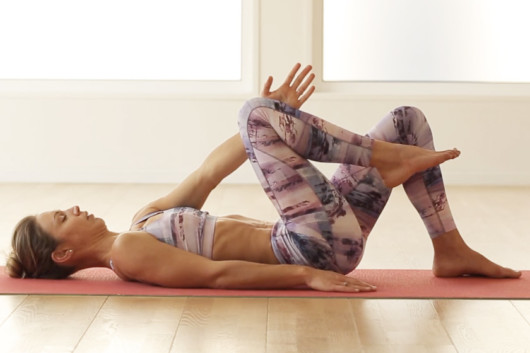A woman is doing postpartum pelvic floor exercises at home