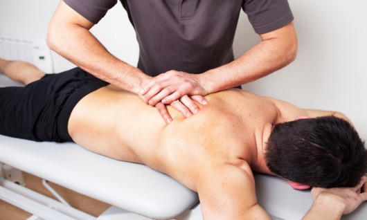 A guy is doing is sport massage to the other guy on the massage bed