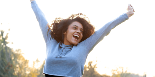A happy girl in blue sweater is smiling and stretching her hands into the air