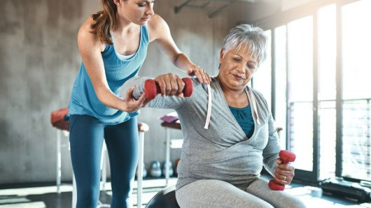 A fitness trainer is helping the old woman to do the exercise with dumbbells. The trainer is instructing the old lady in the gym