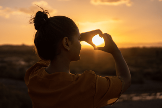 Girl is holding her fingers in the shape of heart in front of the sunset