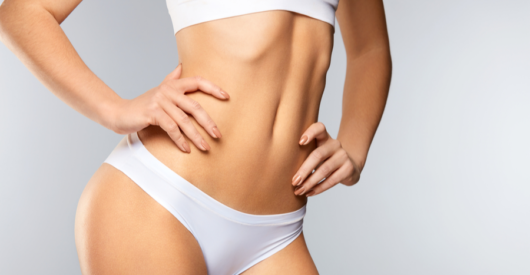 A girl in white underwear on white background shows how her body changed after liposuction procedure.