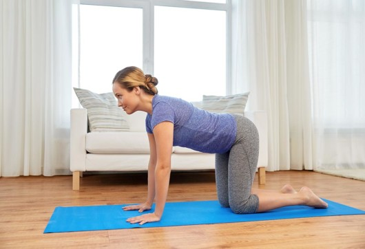 Girl standing on her on hands and knees on the blue mat in the room and exercising