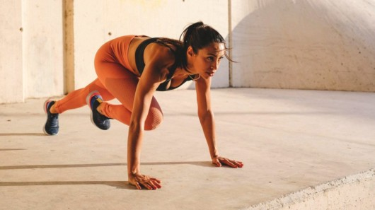 A woman in sportswear doing HIIT workout exercise the floor