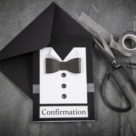 Confirmation invitation layout with a black envelope and scissors and a grey tape on the grey background