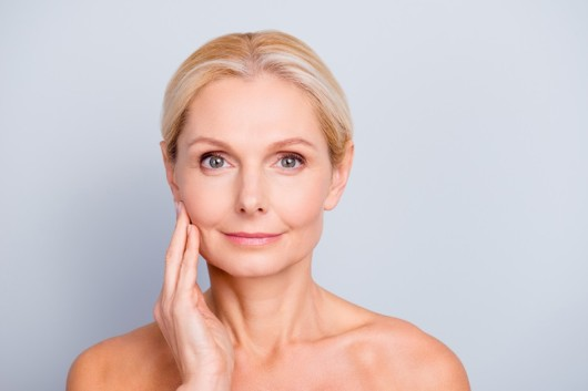 A beautiful middle age woman touching her face after facelift surgery