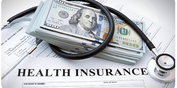 A bundle of banknotes and health insurance form