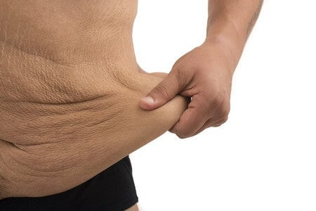 A man on the white background is holding his loose skin throughout the midsection.