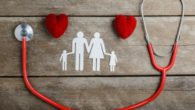 Two hearts, stethoscope and family image are on the wooden background