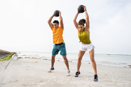 A sporty couple performing HIIT workout with medicine balls on the beach