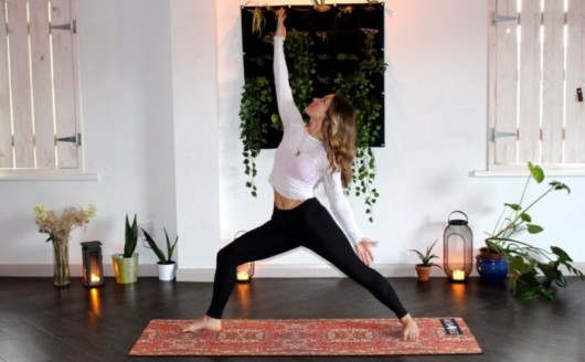 Girl in white top and black leggings are dong yoga in the room