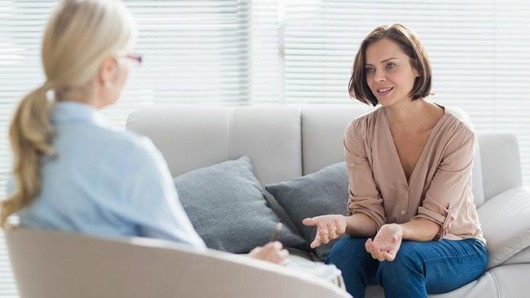 A young woman is sitting on the sofa and talking to a counselor