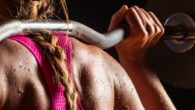 Girl in pink sports bra with barbell on her shoulders ready to workout