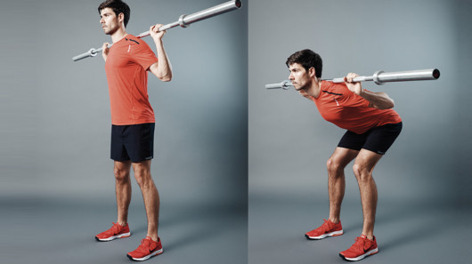 Guy in red t-shirt and black shorts on grey background with a barbell on his shoulders showing how to do good morning exercise
