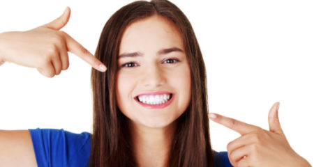 Beautiful woman in blue t-shirt pointing with her fingers at her perfect white teeth on white background