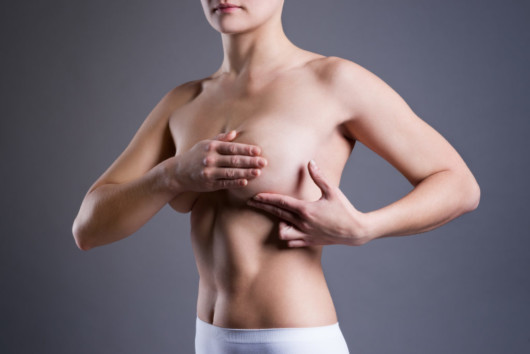 A girl covered her breast with a hand on a grey background