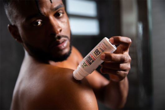 A black man putting CBD cream on his shoulder as a post recovery