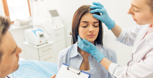 A doctor examining the woman's face after the plastic surgery