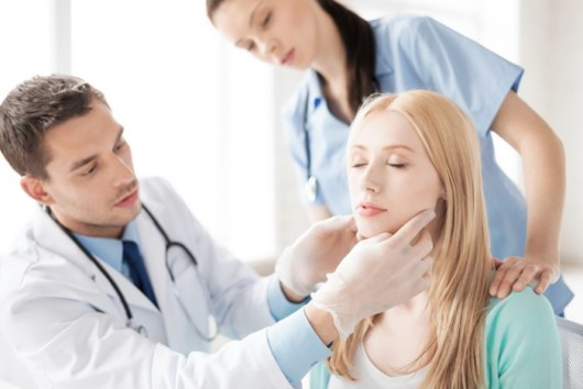 A doctor and a nurse examining the woman's face