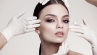 Beautiful girl's face is touched by four hands in white medicine gloves on grey background
