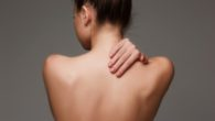 The beautiful woman showing her back on gray background