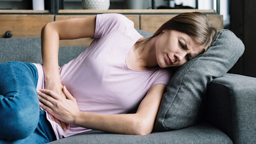 A girl in pink t-shirt and jeans lying on the sofa and holding her stomach in pain