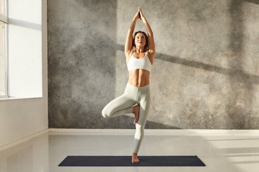A beautiful and lean girl in white outfit is standing in a yoga pose