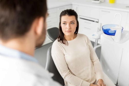 A beautiful girl is sitting in the chair at the dentist's and talking with the doctor before the dental procedure