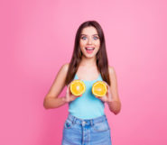 A beautiful girl in blue undershirt and jeans on the pinky background is holding two halves of orange near her breast and smiling