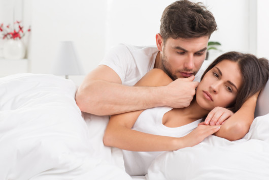 A young couple is lying in a white bed on white background. They are trying to talk. the girl is sad and turned away from the man.