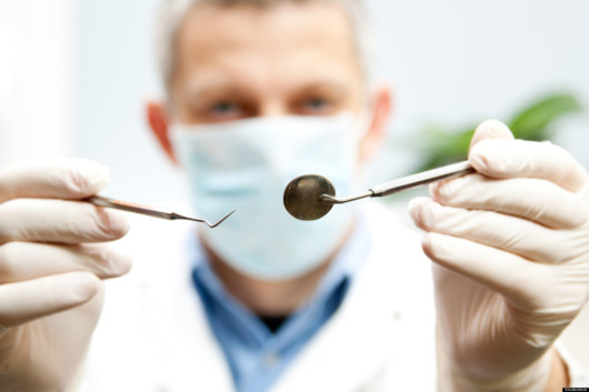 The doctor in face mask is trying to check the teeth with the dental instruments