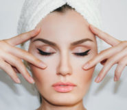 A beautiful face of the girl on the white background. The girl touches her beautiful and young face with her fingers after facial cosmetic procedure